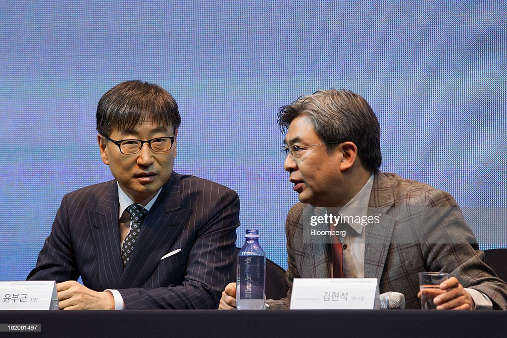 Yoon Boo Keun, president of visual display at Samsung Electronics Co., left, talks with Kim Hyun Suk, vice president of visual display, during a media event in Seoul, South Korea, on Tuesday, Feb. 19, 2013. Samsung Electronics Co., the world's largest television maker, targets to start selling TVs using a technology allowing brighter and sharper images in the first half to extend its market lead. Photographer: SeongJoon Cho/Bloomberg via Getty Images