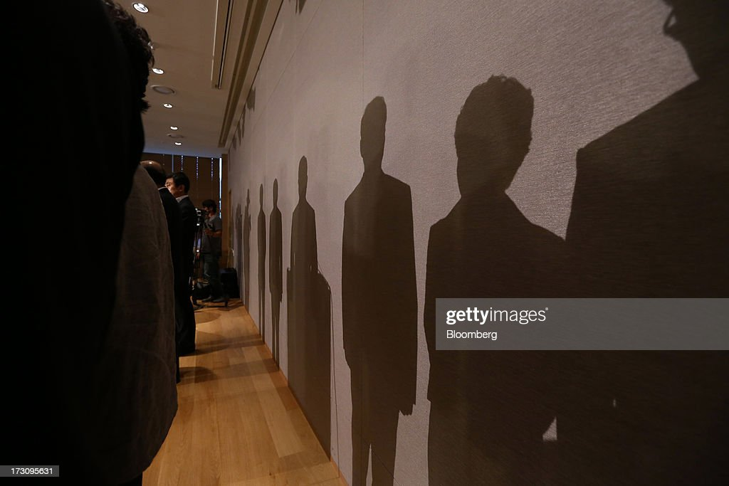 Yoon Young Doo, chief executive officer and president of Asiana Airlines Inc., center, and company executives cast shadows on a wall during a news conference at the company's headquarters in Seoul, South Korea, on Sunday, July 7, 2013. A Boeing Co. 777 flown by South Korea's Asiana Airlines crashed while landing in San Francisco yesterday, killing two people as passengers escaped down emergency slides before a fire swept through the plane. Yoon apologized for the crash and said that Asiana is struggling to confirm details of casualities through the U.S. authorities. Photographer: SeongJoon Cho/Bloomberg via Getty Images