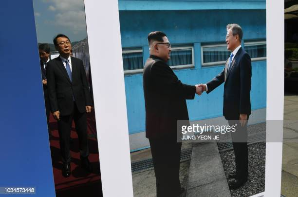 TOPSHOT Yoon Youngchan a senior South Korean presidential secretary for public relations looks at a picture of the summit between South Korean...