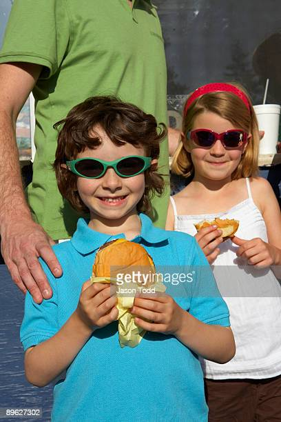 yooung boy and girl holding hamburgers  - jason todd stock photos and pictures