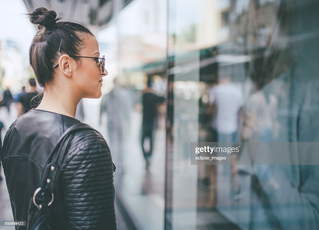 yooung woman looking at shop windows : Stock Photo