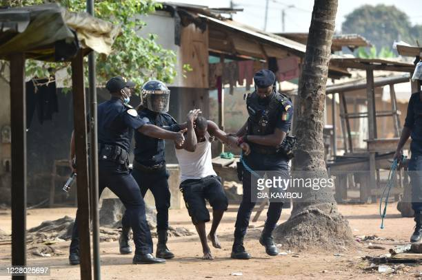 TOPSHOT Yopougon municipal police officers arrest a man during a protest against the third term of Ivory Coast President Alassane Ouattara in the...