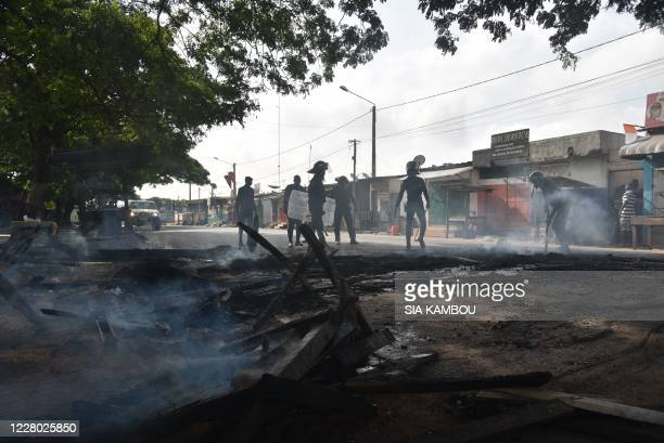 Yopougon municipal police officers clear debris from the road that was placed there by young demonstrators during a protest against the third term of...