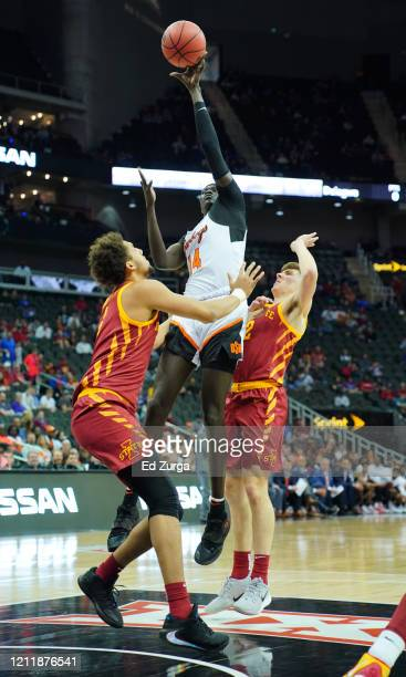 Yor Anei of the Oklahoma State Cowboys shoots between George Conditt IV and Caleb Grill of the Iowa State Cyclones in the first half during the first...