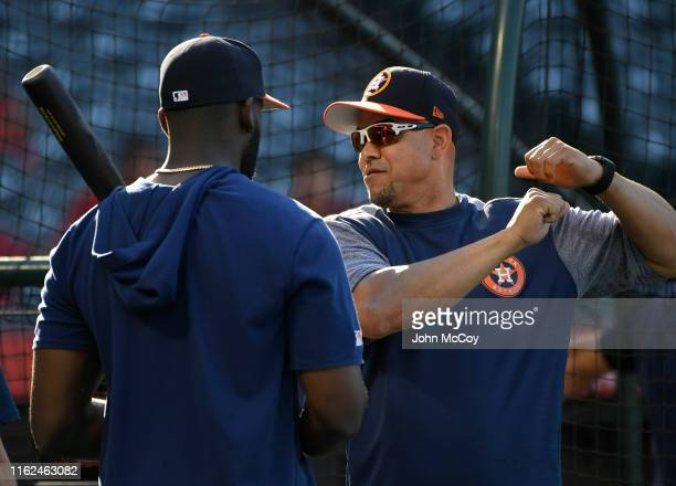 Yordan Alvarez listens as hitting coach Alex Cintron of the Houston Astros gives advice before playing the Los Angeles Angels of Anaheim at Angel...