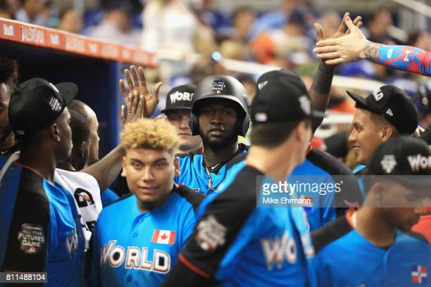Yordan Alvarez of the Houston Astros and the World Team celebrates in the dugout after scoring in the ninth inning during the SiriusXM AllStar...