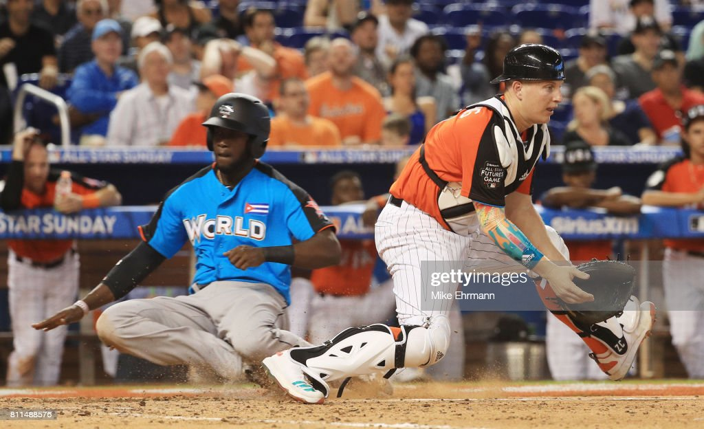 Yordan Alvarez #43 of the Houston Astros and the World Team slides in safely past Zack Collins #8 of the Chicago White Sox and the U.S. Team during the SiriusXM All-Star Futures Game at Marlins Park on July 9, 2017 in Miami, Florida.