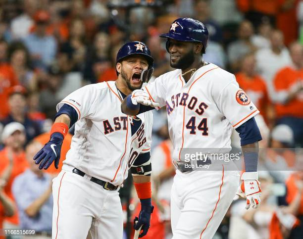 Yordan Alvarez of the Houston Astros celebrates with Yuli Gurriel after hitting a home run in the second inning against the Colorado Rockies at...