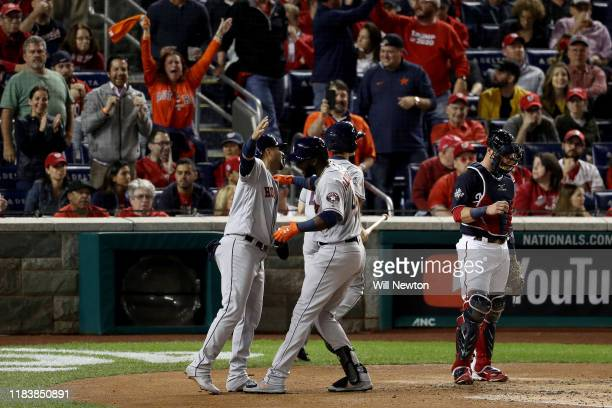 Yordan Alvarez of the Houston Astros is congratulated by his teammate Yuli Gurriel after hitting a tworun home run against the Washington Nationals...