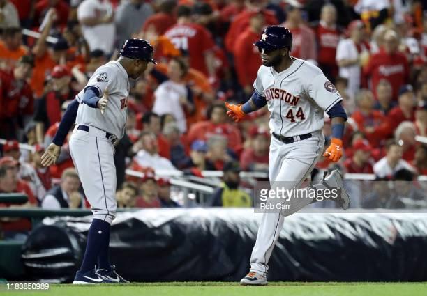 Yordan Alvarez of the Houston Astros is congratulated by his third base coach Gary Pettis after hitting a tworun home run against the Washington...