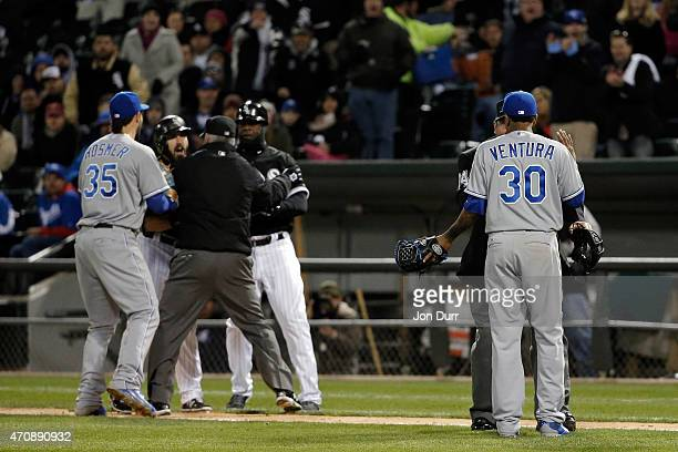 Yordano Ventura of the Kansas City Royals talks to umpire Sam Holbrook while umpire Tim Timmons and first base coach Daryl Boston of the Chicago...