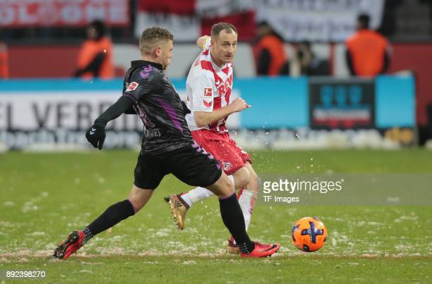 Yoric Ravet of Freiburg and Matthias Lehmann of Koeln battle for the ball during the Bundesliga match between 1 FC Koeln and SportClub Freiburg at...