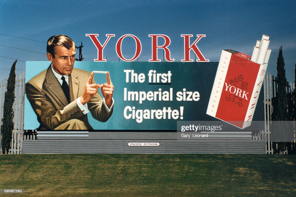 York Cigarette with an elegant man in a brown suit holding a cigarette between his index fingers in 1962 in Los Angeles, California. York cigarette billboard from the 1950's