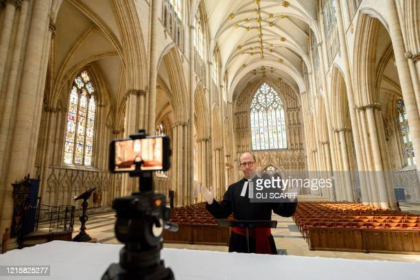 York Minster's Canon Pastor Reverend Michael Smith rehearses the weekly broadcast of the Minster's new digital Evensong service in the otherwise...