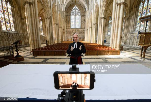 York Minster's Canon Pastor, Reverend Michael Smith rehearses the weekly broadcast of the Minster's new digital Evensong service in the otherwise...