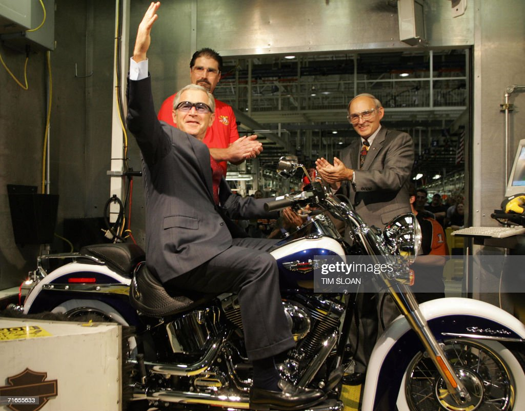 US President George W. Bush (C) sits on a motorcycle in the 'roll test' booth joined by Jim Ziemer (R), President and CEO of Harley-Davidson Inc. and Joel Toner (L), test operator 16 August, 2006 at the Harley-Davidson assembley plant in York, Pennsylvania, which employs some 3,200 people.