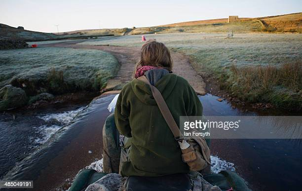 Yorkshire shepherdess Amanda Owen rides her quad bike through a river as she heads out to feed her Swaledale sheep on April 15 2014 near Kirkby...