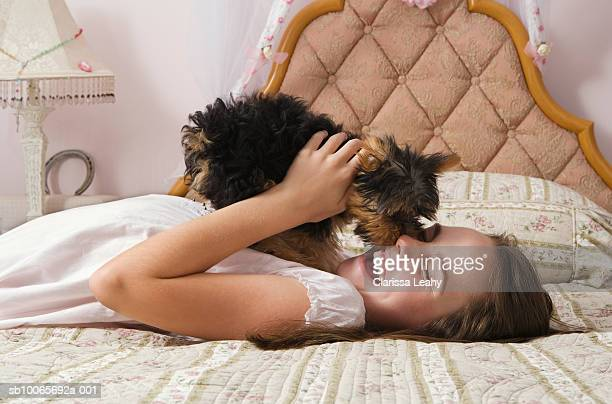 Yorkshire terrier puppy licking face of girl (10-11) on bed