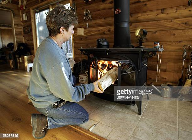 Ann Undesser loads a wood burning stove 24 October 2005 at her residence in Yorkville Illinois which along with two corn burning stoves she plans on...