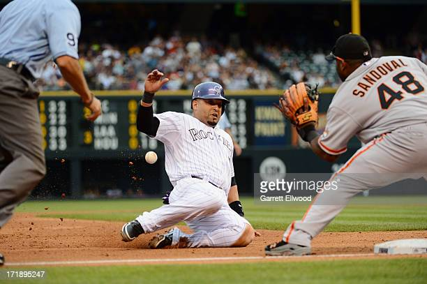 Yorvit Torrealba of the Colorado Rockies slides safely into third base against Pablo Sandoval of the San Francisco Giants during the game at Coors...