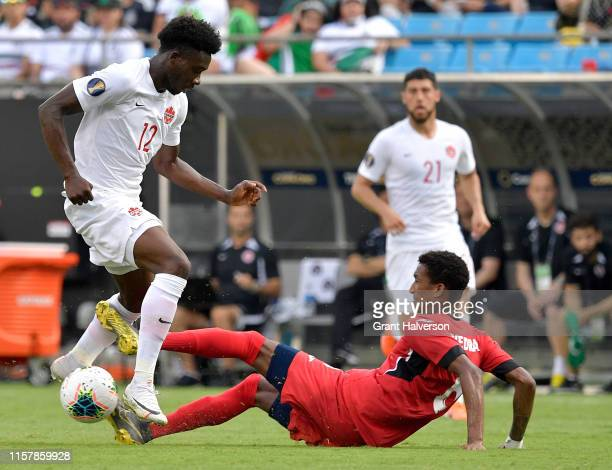 Yosel Piedra of Cuba tackles Alphonso Davies of Canada during the second half of their Group A 2019 CONCACAF Gold Cup match at Bank of America...