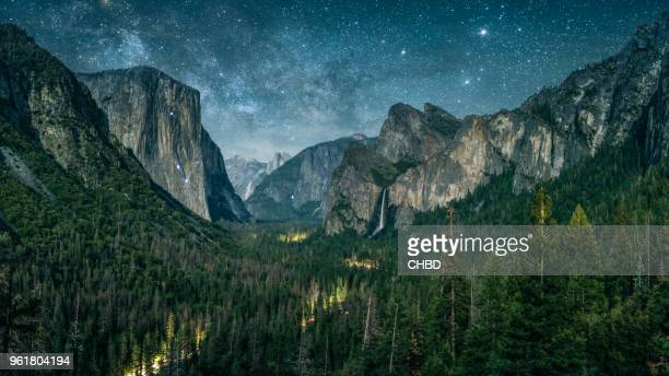 yosemite illuminated by waxing crescent moonlight with rising milky way. - yosemite valley stock photos and pictures