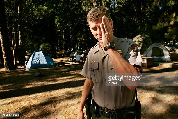 Yosemite Valley CA Keith Lober the US Park Ranger/Paramedic Emergency Services Coordinator in Yosemite National Park wipes mosquitoes as he walks...
