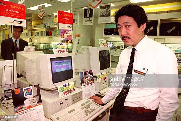 Yoshiaki Matsuzaki 4th floor Assistant Manager of Laox Computer Store poses in front of Americanmade IBM PC/AT compatible computers at the store in...