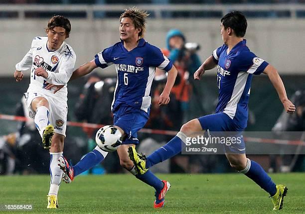 Yoshiaki Ohta of Vegalta Sendaion challenges Jiang Jiajun and Ren Hang of Jiangsu Sainty during the AFC Champions League match between Jiangsu Sainty...