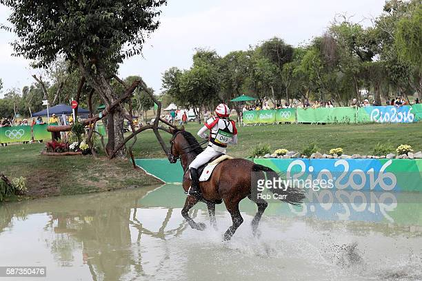 Yoshiaki Oiwa of Japan riding The Duke Of Cavan rides through a water obstacle during the Cross Country Eventing on Day 3 of the Rio 2016 Olympic...