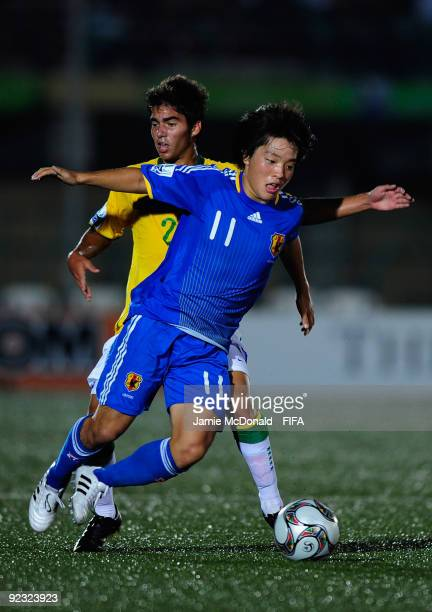Yoshiaki Takagi of Japan battles with Crystian of Brazil during the FIFA U17 World Cup match between Brazil and Japan at the Teslim Balogun Stadium...