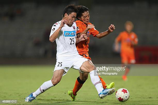Yoshiaki Takagi of Shimizu S-Pulse and Kazuki Kushibiki of Consadole Sapporo compete for the ball during the Emperor's Cup third round match between...