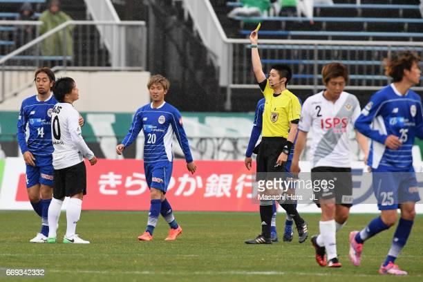 Yoshiaki Takagi of Tokyo Verdy is shown a yellow card by referee Kazuyoshi Enomoto during the J.League J2 match between Montedio Yamagata and Tokyo...