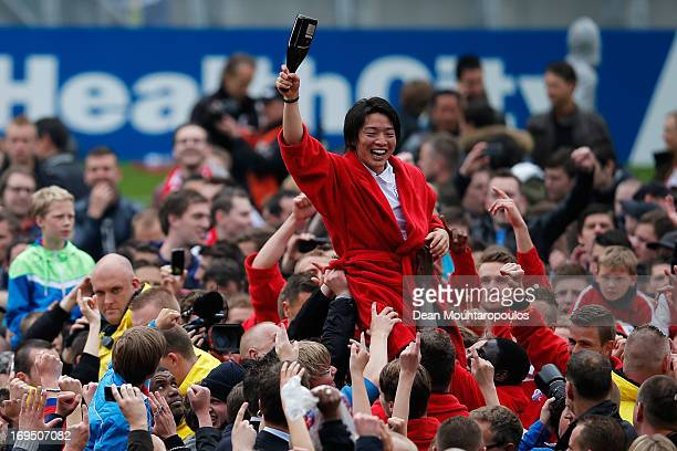 Yoshiaki Takagi of Utrecht celebrates with team mates as the fans cheer his name after winning the Eredivisie Europa League Play off match between FC...