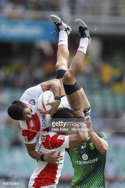 Yoshiaki Tsurugasaki of Japan is held up by Dai Ozawa of Japan after he take a ball from the kickoff during the Men Pool A match between Japan and...