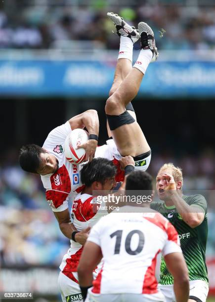 Yoshiaki Tsurugasaki of Japan is held up by Dai Ozawa of Japan after taking a ball from a restart during the mens pool match between South Africa and...
