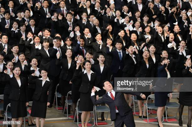 Yoshiharu Ueki president of Japan Airlines Co front row center and new employees release paper airplanes during an initiation ceremony at one of the...