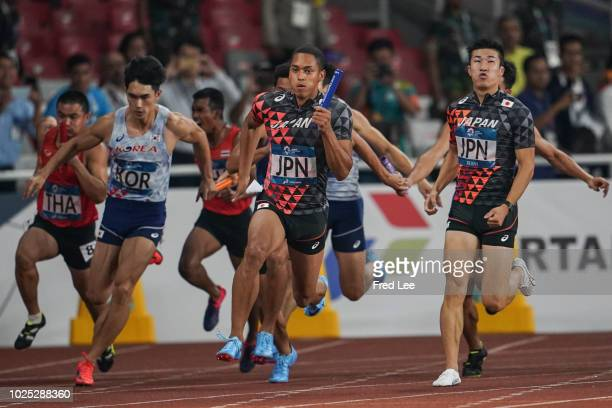Yoshihide Kiryu and Aska Antonio Cambridge of Japan in action the final of the men's 4*100m athletics event during on day twelve of the Asian Games...