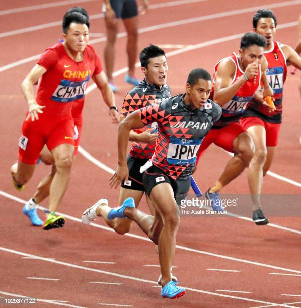 Yoshihide Kiryu and Aska Cambridge of Japan compete in the Men's 4x100m Relay at the GBK Main Stadium on day twelve of the Asian Games on August 30...