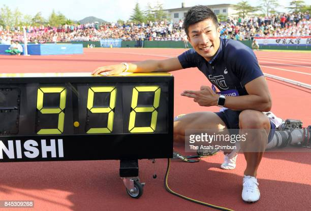 Yoshihide Kiryu of Toyo University poses for photographs with the electric board displaying 998 second after winning the Men's 100m final during day...