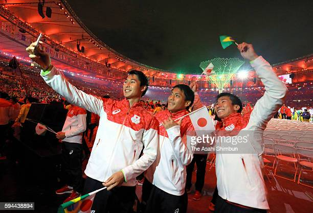 Yoshihide Kiryu Shota Iizuka and Ryota Yamagata pose for selfie photographs during the Closing Ceremony on Day 16 of the Rio 2016 Olympic Games at...