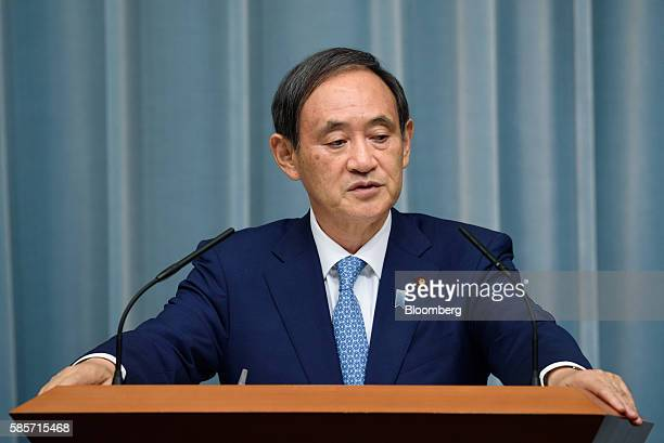 Yoshihide Suga, chief cabinet secretary of Japan, listens during a press conference at the official residence of Japan's Prime Minister Shinzo Abe,...