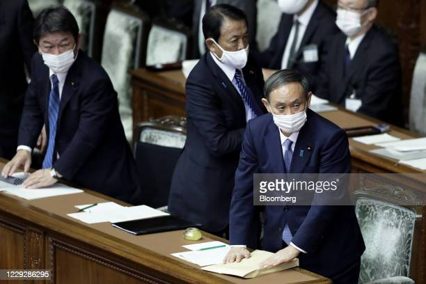Yoshihide Suga, Japan's prime minister, from right, and Taro Aso, deputy prime minister and finance minister, wear protective face masks as they...
