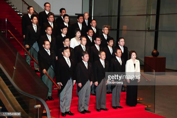 Yoshihide Suga, Japan's prime minister, front row center, poses for a group photograph with his new cabinet members at his official residence in...