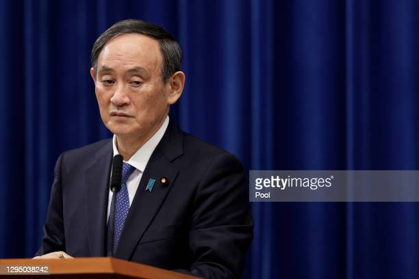 Yoshihide Suga, Japan's prime minister, listens during a news conference at the prime minister's official residence on January 07, 2021 in Tokyo,...