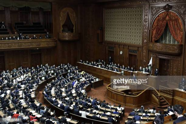 Yoshihide Suga, Japan's prime minister, wears a protective face mask as he delivers his policy speech during an extraordinary session at the lower...