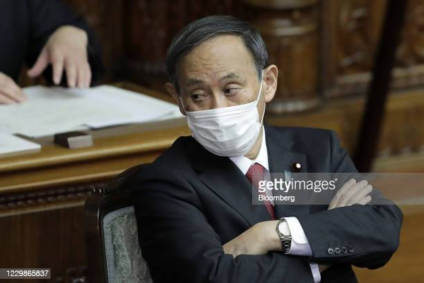 Yoshihide Suga, Japan's prime minister, wears a protective face mask as he attends a plenary session at the upper house of parliament in Tokyo,...