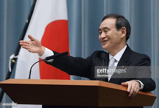Yoshihide Suga, Japan's re-appointed chief cabinet secretary, points to a reporter during a news conference at the prime minister's official...