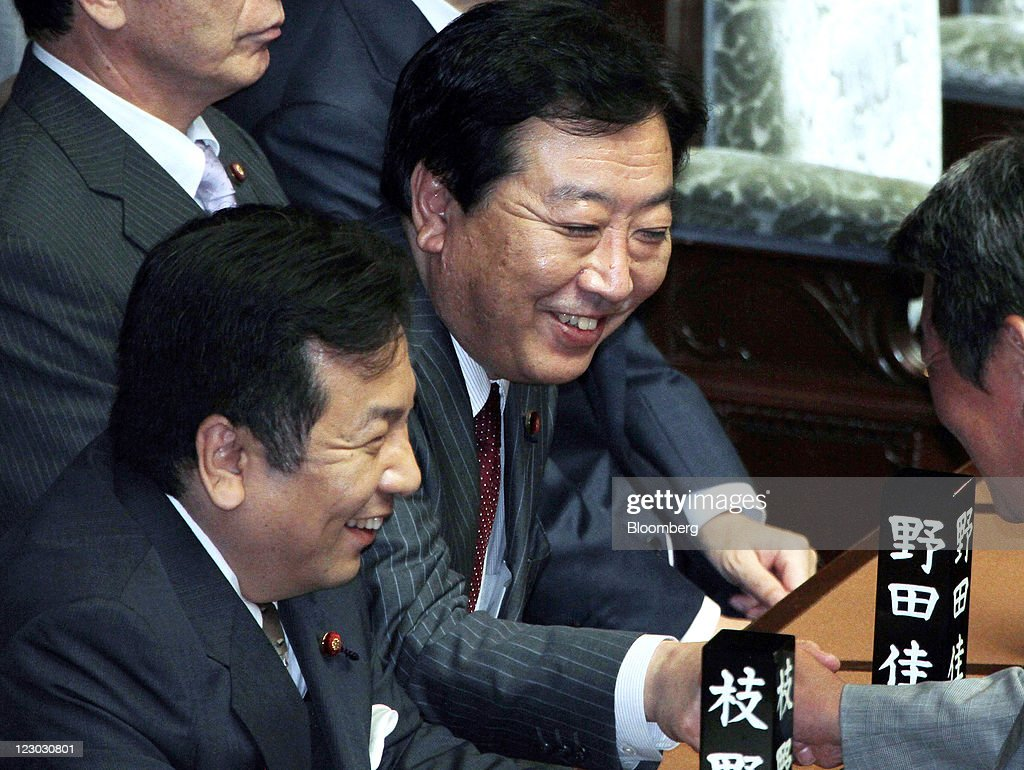 Yoshihiko Noda, president of the Democratic Party of Japan (DPJ) and Japan's newly named prime minister, center, smiles during a meeting at the lower house of parliament in Tokyo, Japan, on Tuesday, Aug. 30, 2011. Noda becomes Japan's sixth leader in five years, seeking a consensus to raise taxes to pay for rebuilding from the March earthquake and nuclear disaster and reduce the world's largest debt. Photographer: Haruyoshi Yamaguchi/Bloomberg via Getty Images