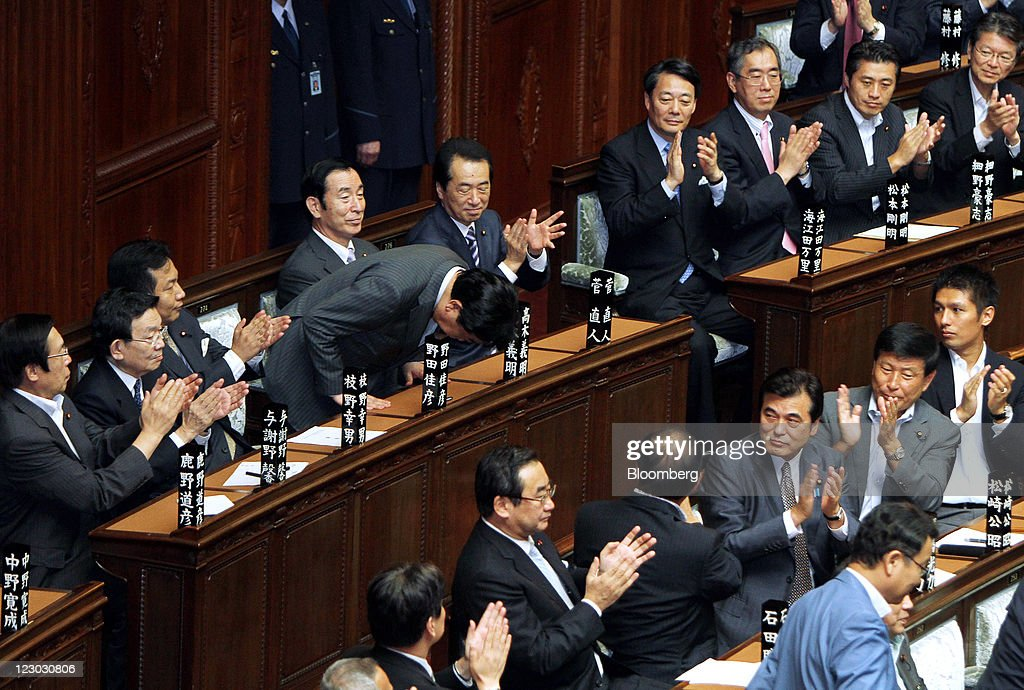 Yoshihiko Noda, president of the Democratic Party of Japan (DPJ), standing fourth from left, bows after being elected Japan's prime minister at the lower house of parliament in Tokyo, Japan, on Tuesday, Aug. 30, 2011. Noda becomes Japan's sixth leader in five years, seeking a consensus to raise taxes to pay for rebuilding from the March earthquake and nuclear disaster and reduce the world's largest debt. Photographer: Haruyoshi Yamaguchi/Bloomberg via Getty Images